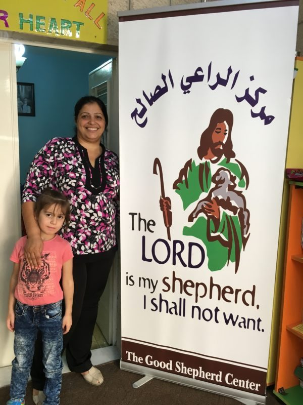 The Principle of the school and a young student pose with a banner outside the school.