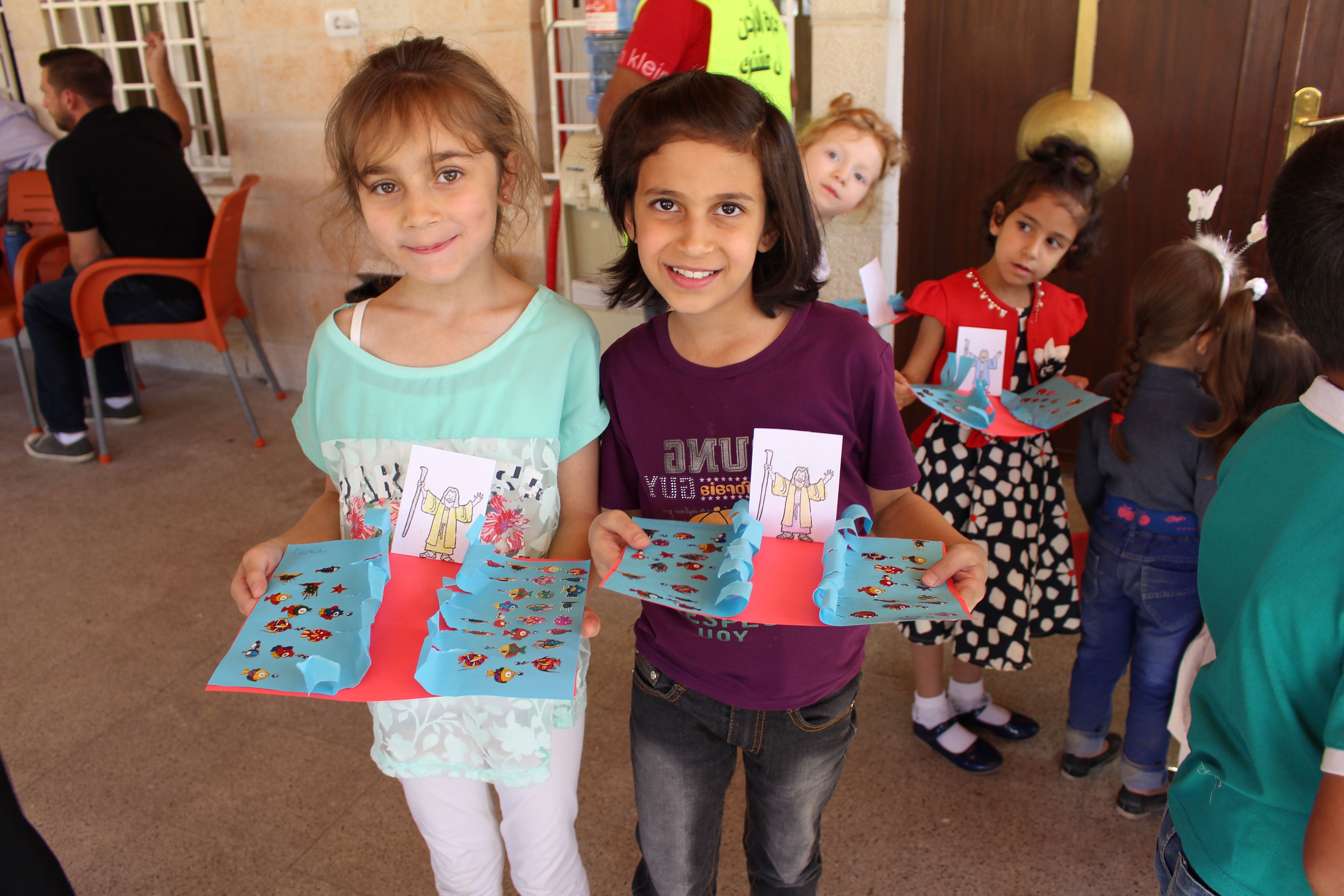 Two little girls pose with their Moses parting the Red Sea crafts.